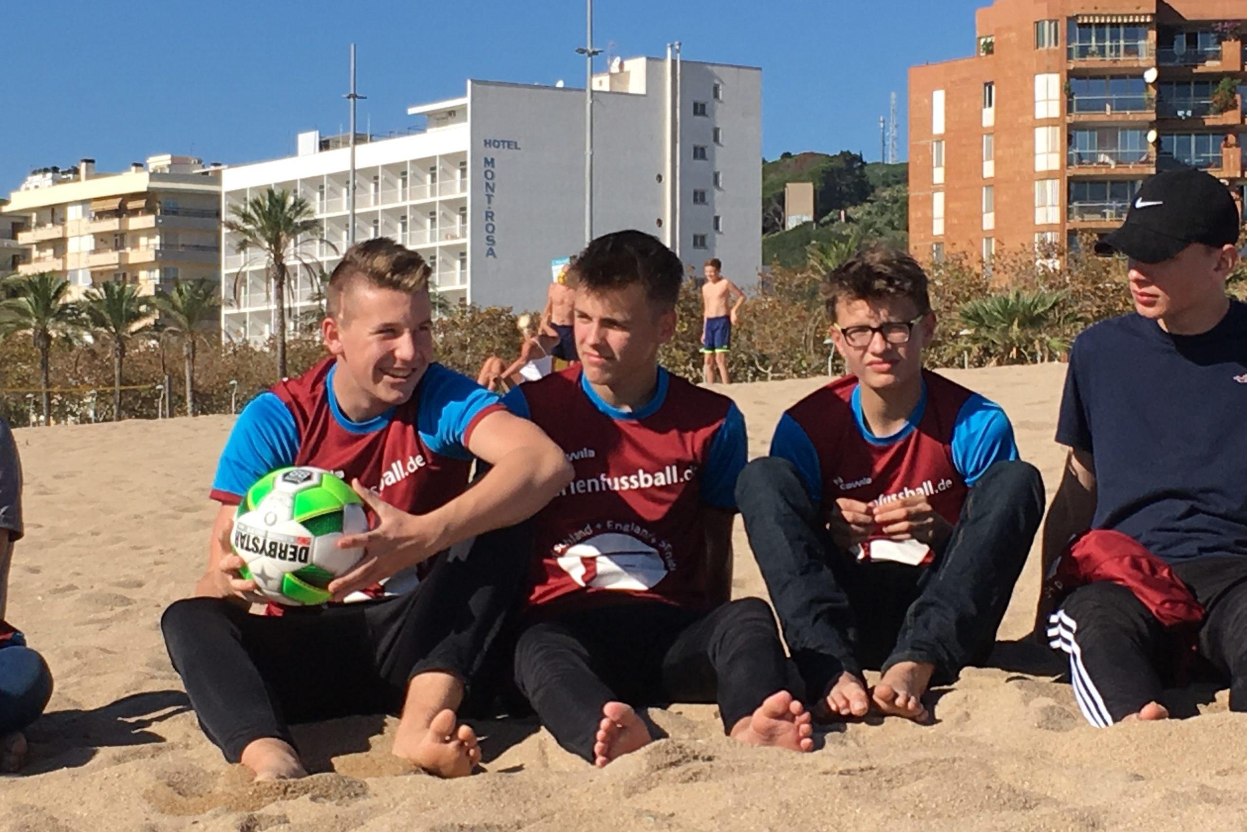 Jungen sitzen mit Ball am Strand