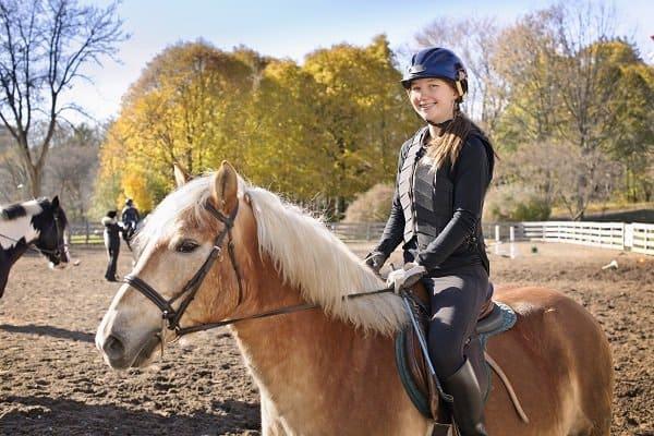 Junges Mädchen auf dem Pferd am Reiten