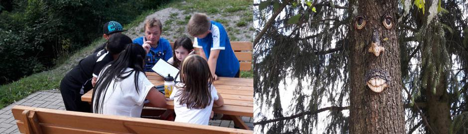 Kinder stecken Köpfe im Wald zusammen und Baumgesicht