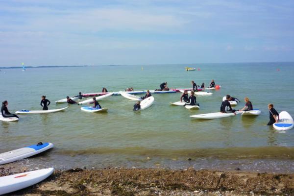 Viele Kinder sitzen auf Surfboards im Wasser