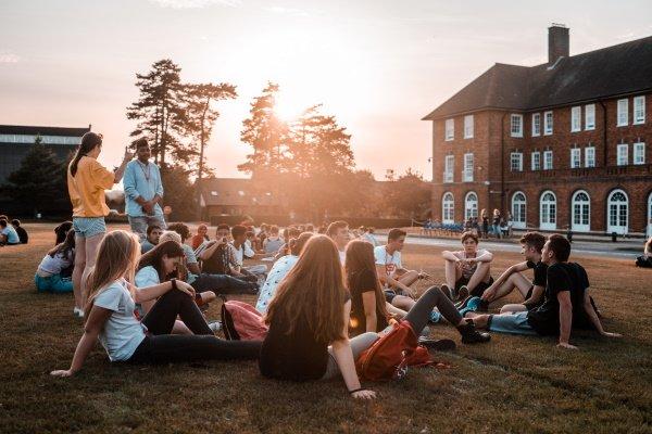 Jugendliche sitzen auf einer Wiese in England