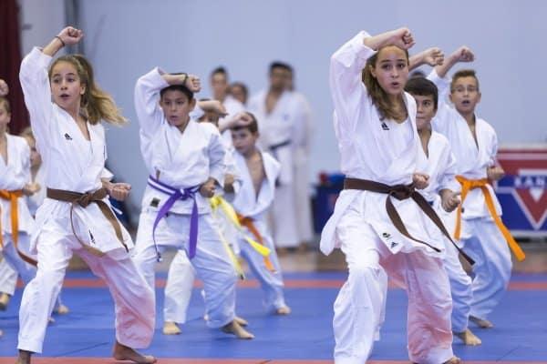 Gruppe Kinder mit Lehrer machen Kampfsport in Halle