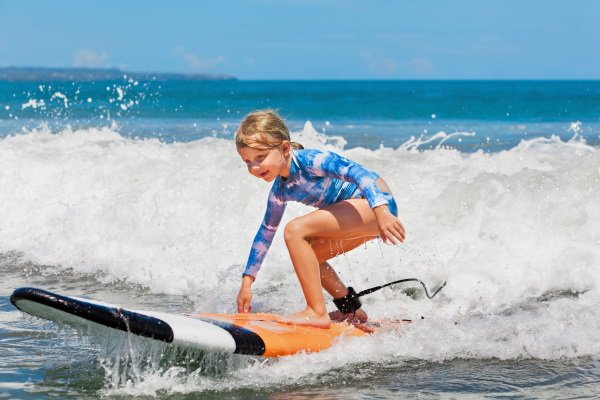 Mädchen steht auf Surfbrett und surft im Meer eine Welle