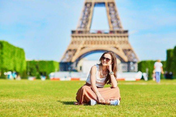 Mädchen sitz vor dem Eifelturm in Frankreich