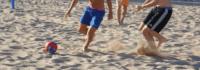 Jungen beim Fußballspielen am Strand