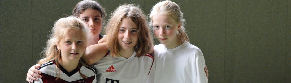 Vier Mädchen lachen in die Kamera