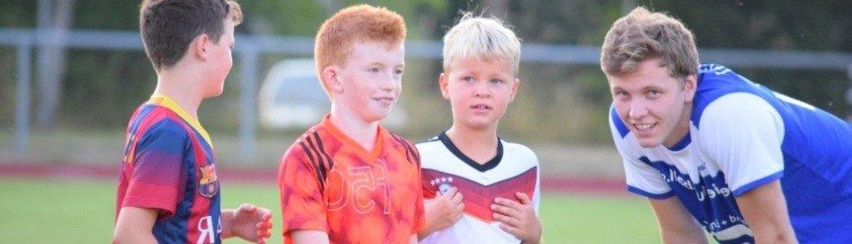 Kinder und Trainer auf dem Fußballplatz