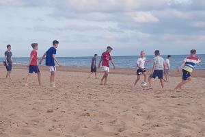 Jugendliche spielen Fußball am Strand