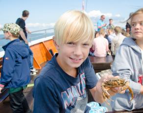Kind mit einer Krabbe in der Hand