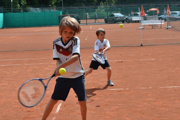 Kleiner Junge returniert den Ball im Tenniscamp