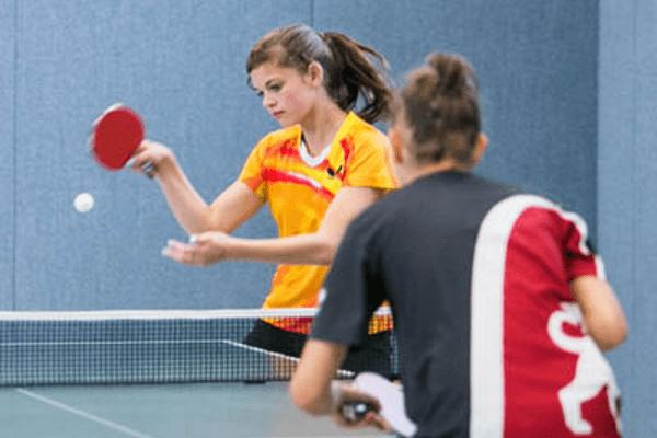Mädchen macht Tischtennisaufschlag
