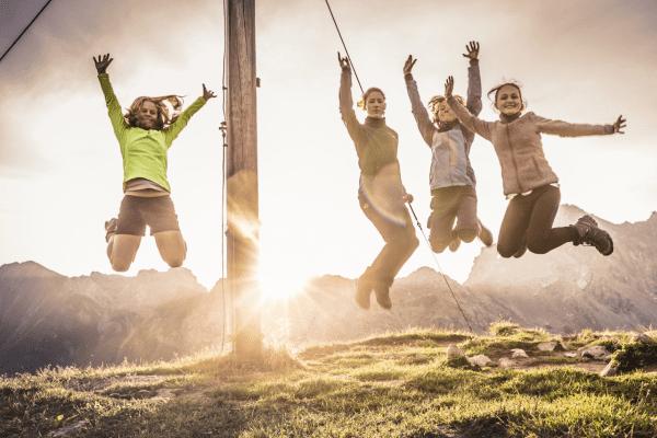 Mädchen springen am Gipfekkreuz