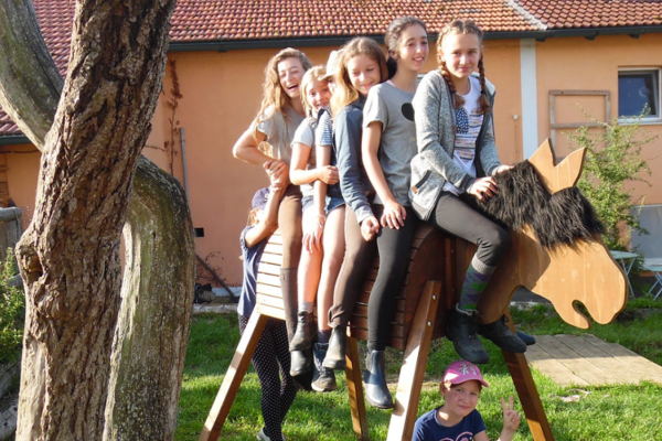 fünf Mädchen auf Holzpferd