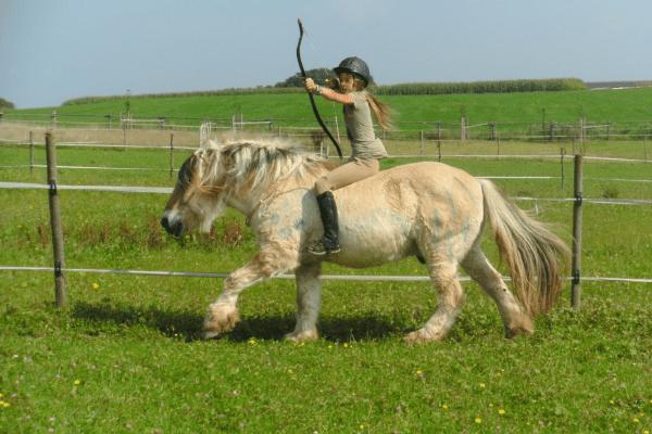 Mädchen mit Pfeil und Bogen auf Pferd
