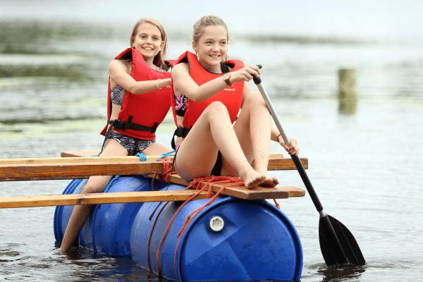 Zwei Mädchen auf Tonne im Wasser